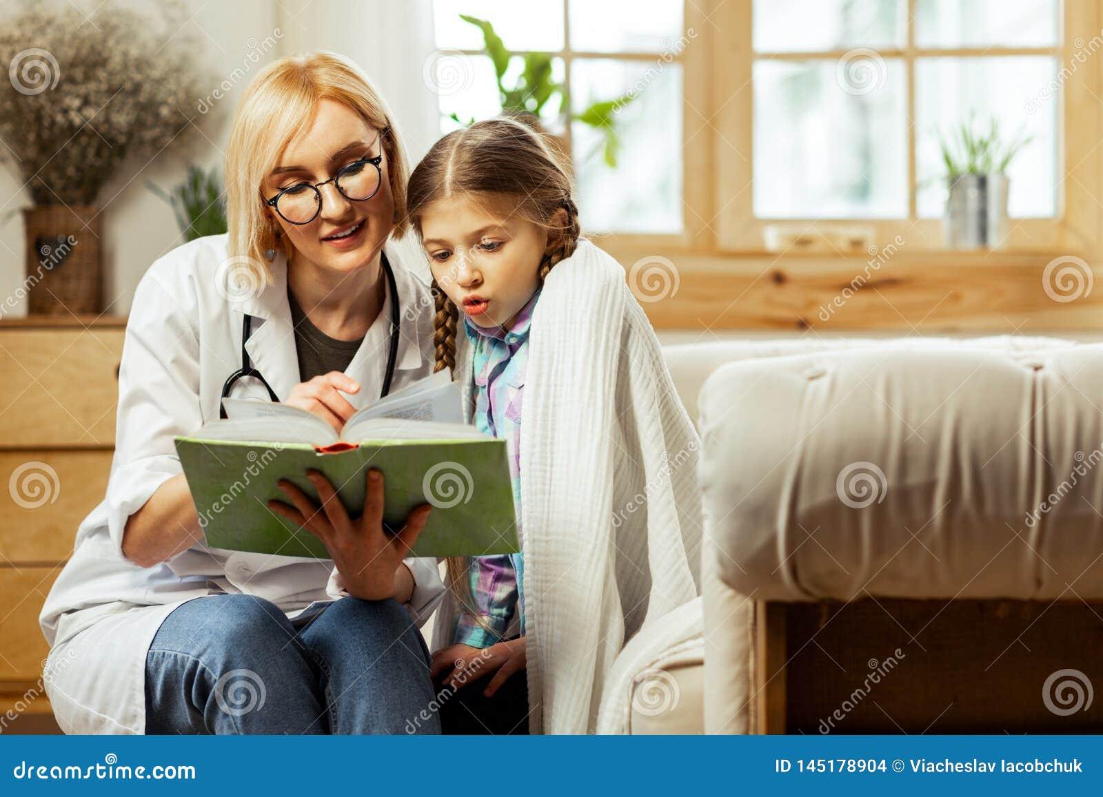 Médico de fascínio que lê um livro criançola com uma menina doente bonito