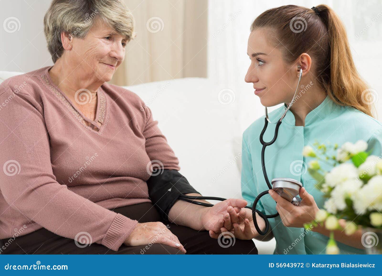 Médico joven que toma la presión arterial