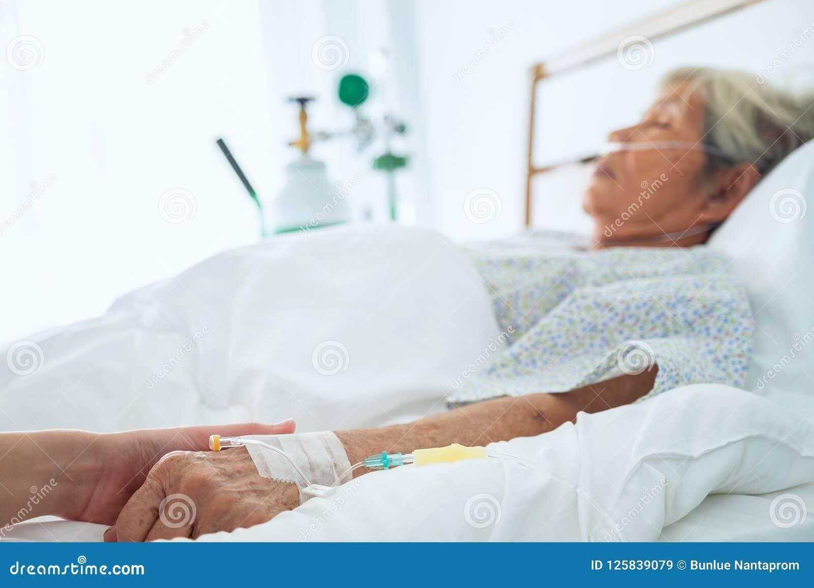 Médico que fura as mãos pacientes superiores do ` s e que consola a,