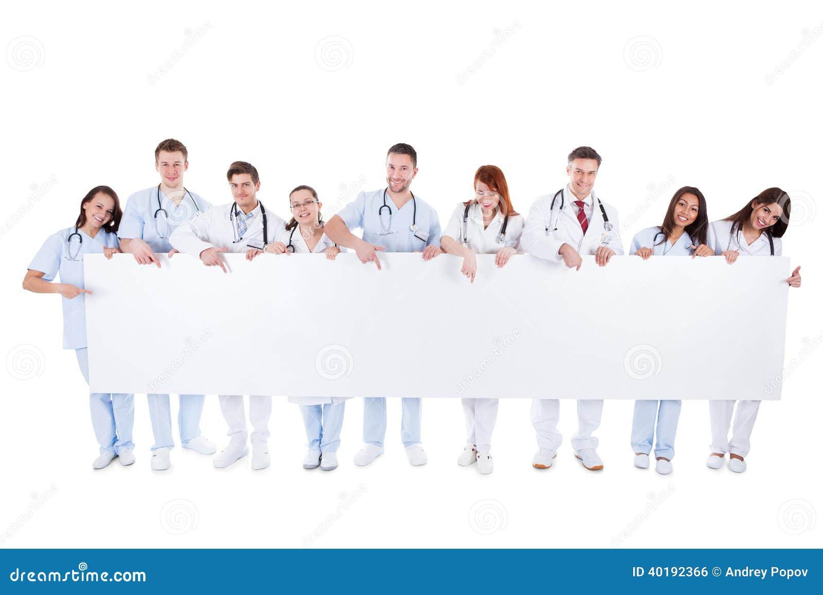 Médicos amistosos que sostienen una bandera en blanco