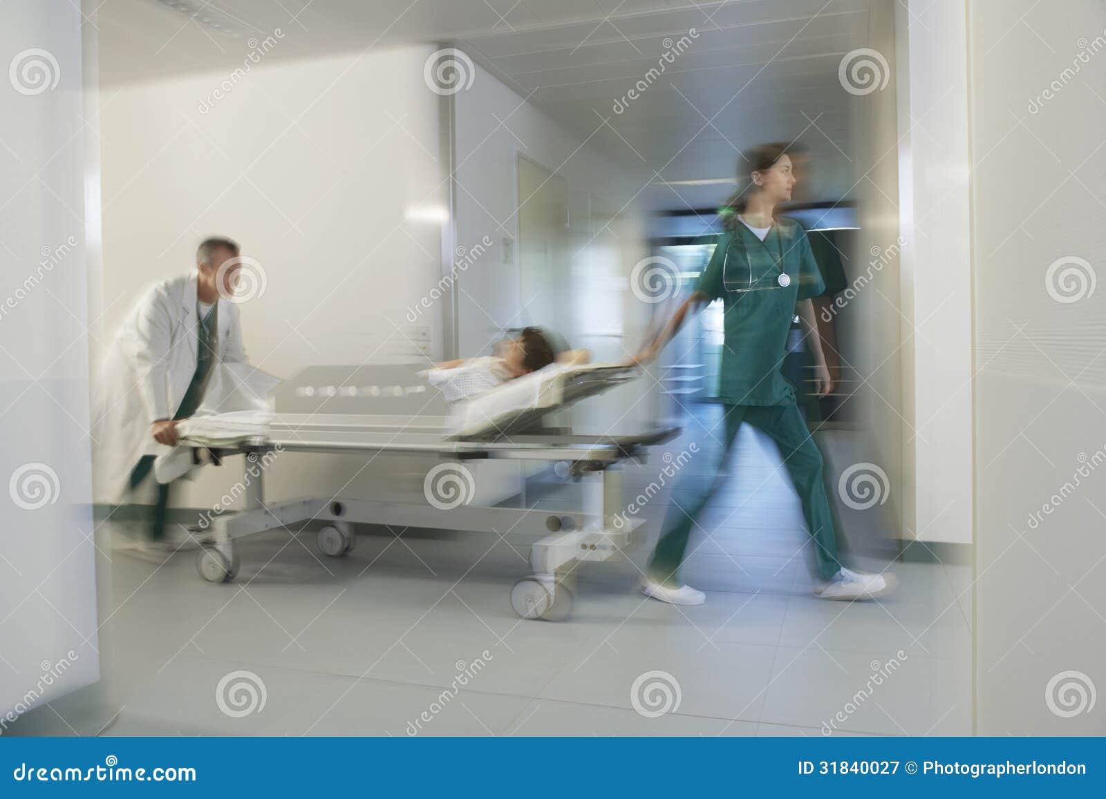 Médicos que mueven al paciente en la camilla a través del pasillo del hospital