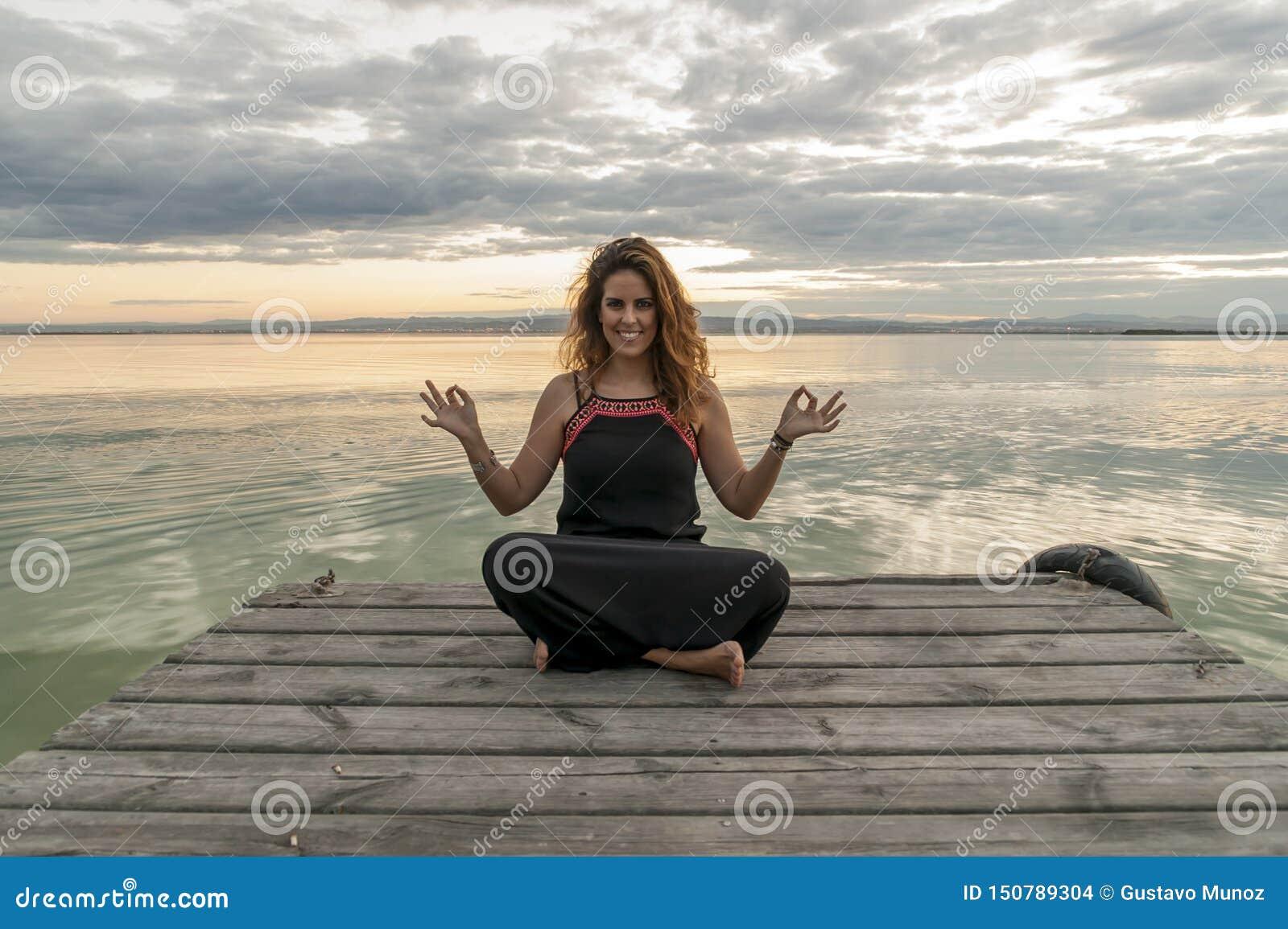 Méditation de pratique de sourire de femme en position de yoga de lotus sur une jetée en bois