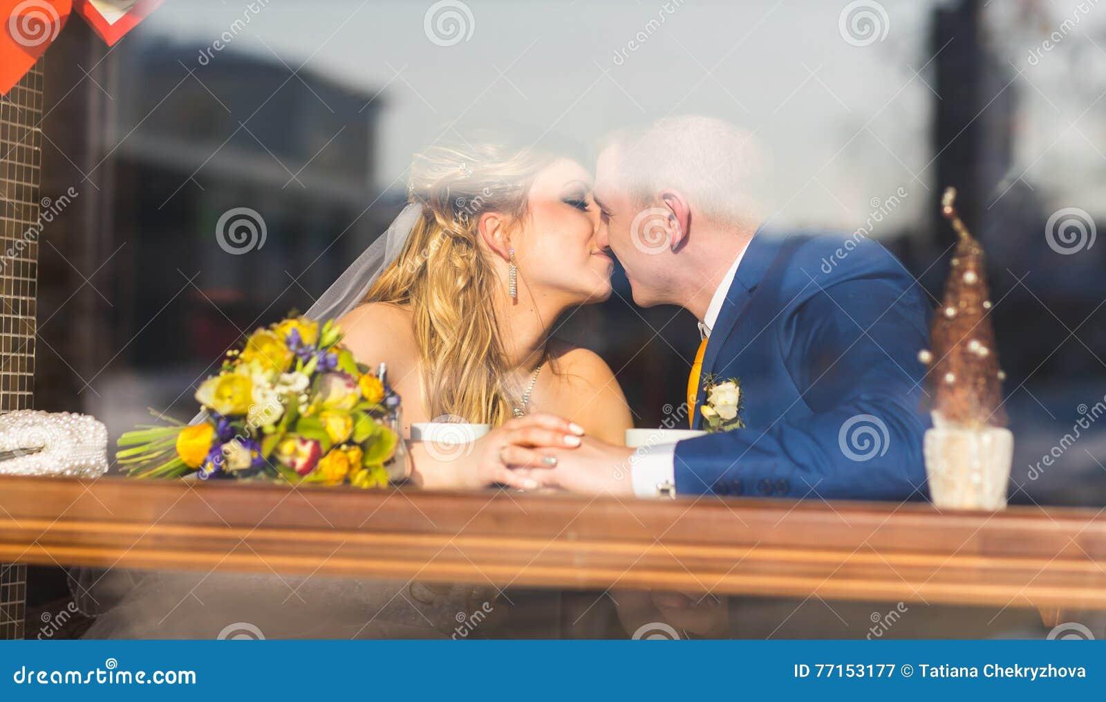Ménages mariés mignons en café, marié embrassant une jeune mariée Tendresse pure