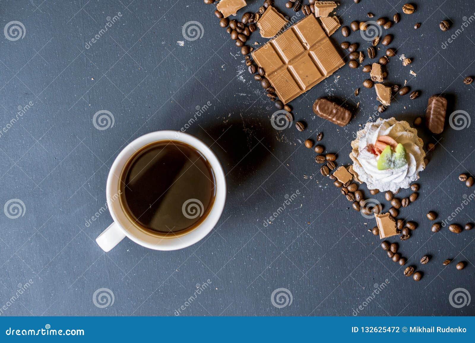Même le café avec des bonbons et des biscuits sur la table foncée f