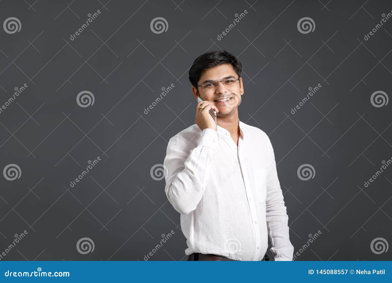 Móvil indio joven de la tenencia del hombre a disposición