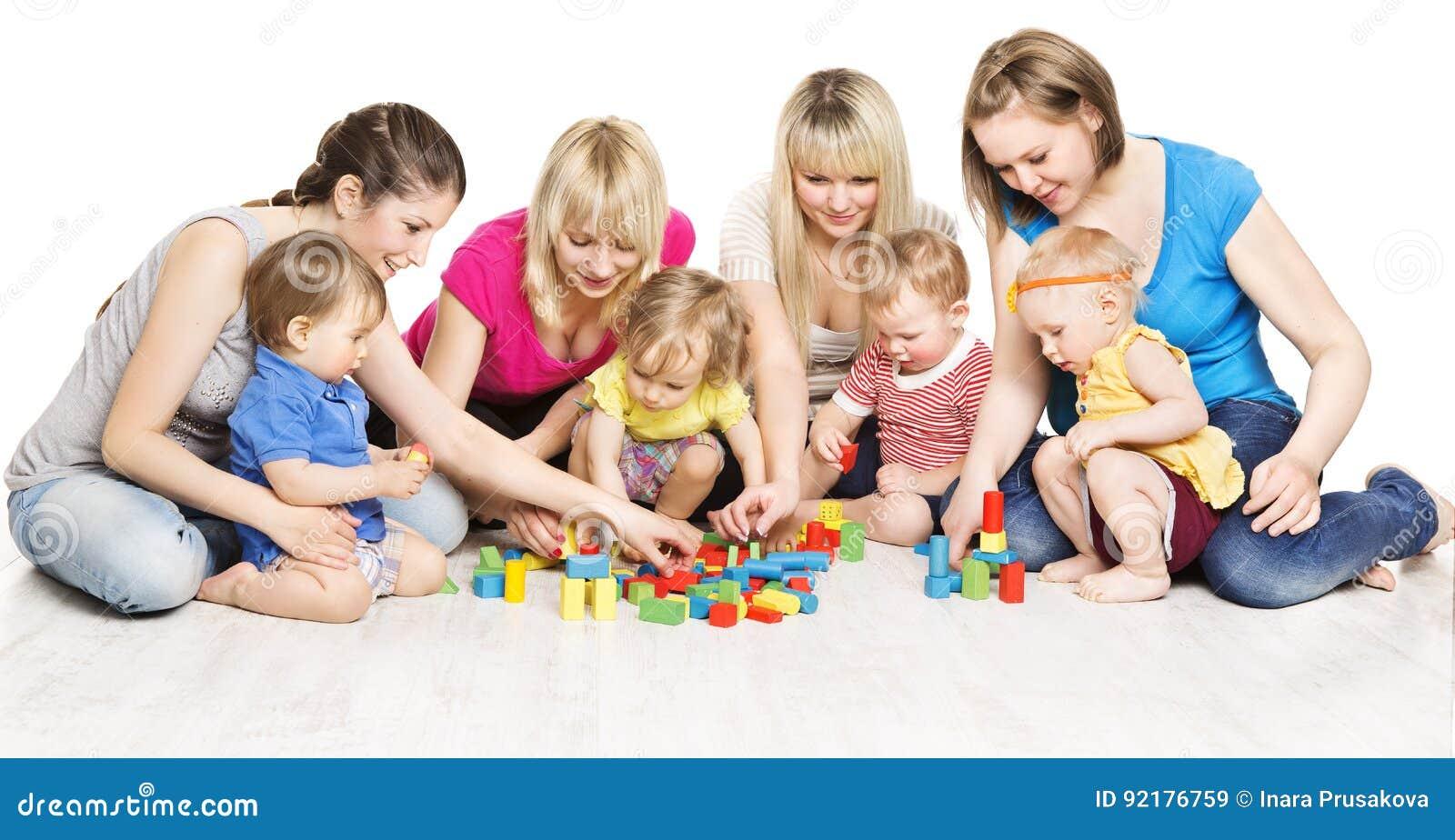 Mödrar och ungegruppen som spelar leksaker, moderlek med, behandla som ett barn