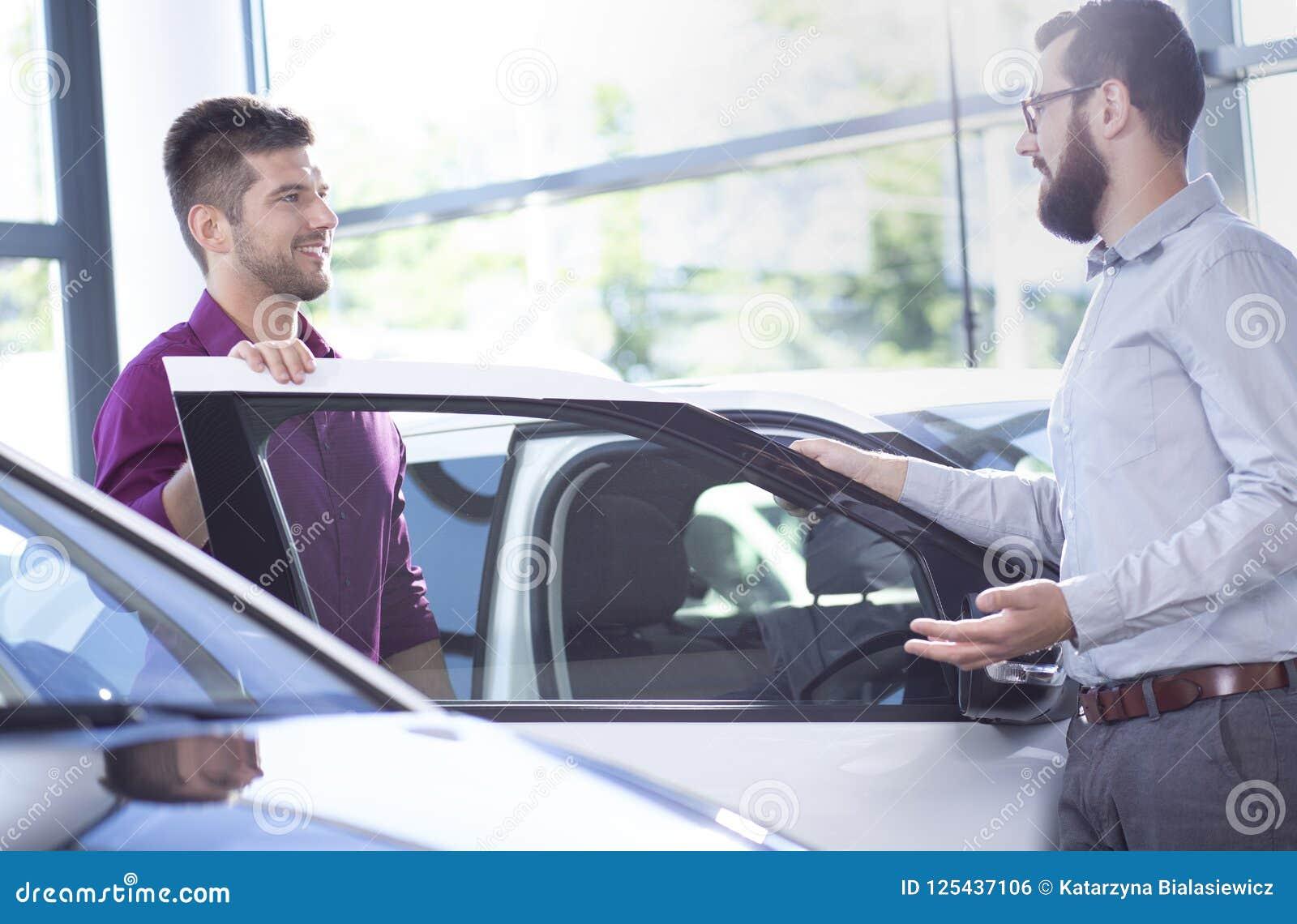 Möglicher Käufer, der mit einem Autohändler nahe bei einem Auto spricht