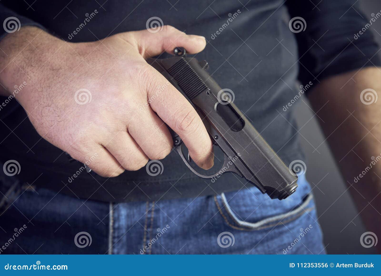Mördare som rymmer en vapensida honom, kantjusterat skott av det hållande vapnet för man i hand