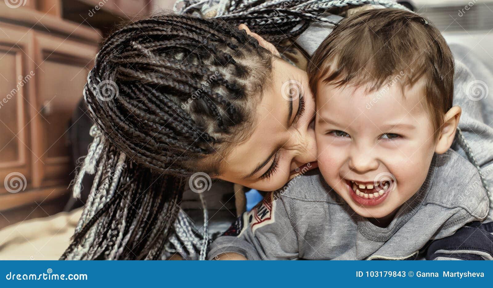 Mörkhyade moderlekar med hennes son Latin - amerikanska mammalekar och skratt med hans lilla son Begrepp: Lycklig dag för moder`