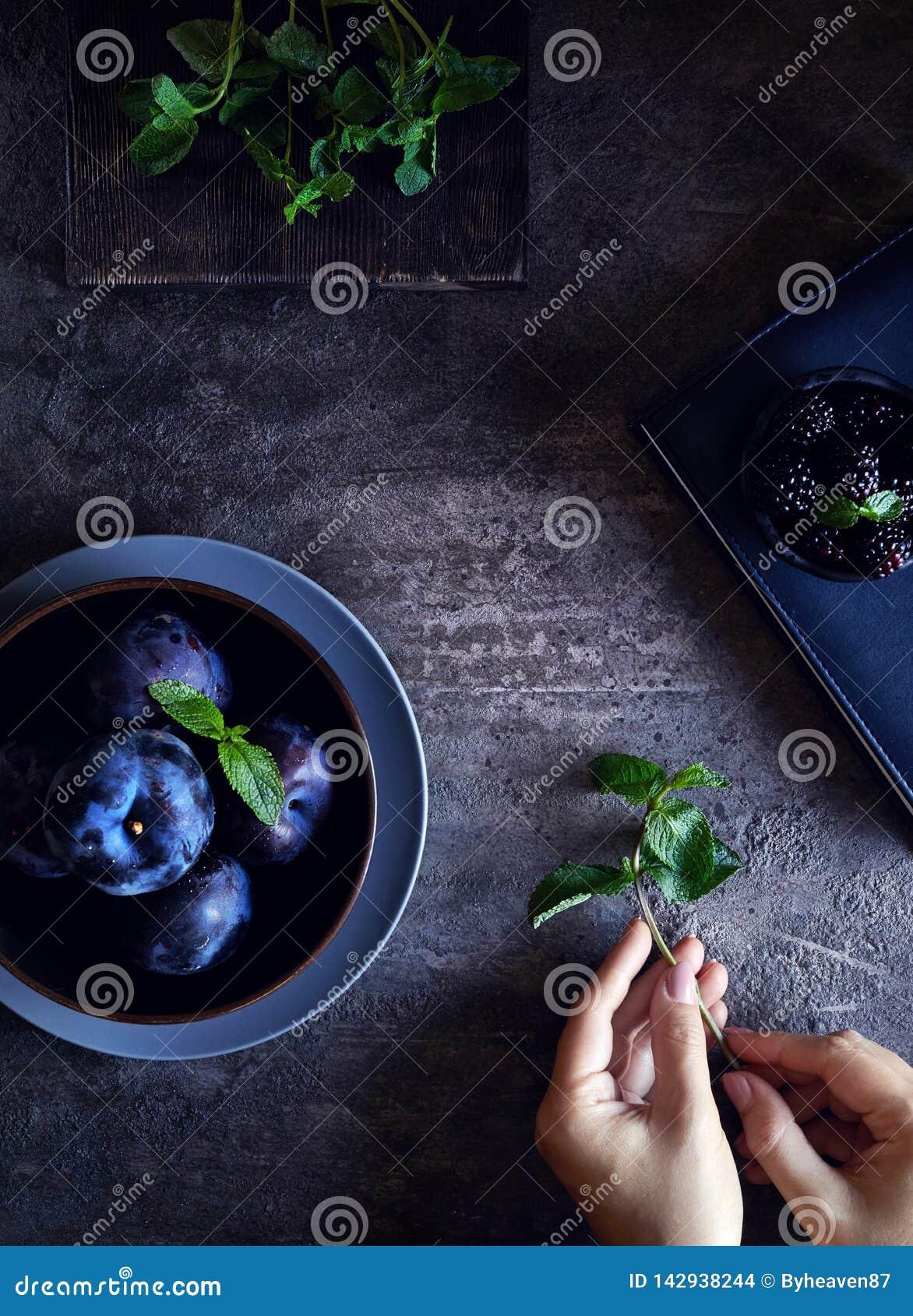 Mörkt matfoto med björnbäret, plommoner och mintkaramellen