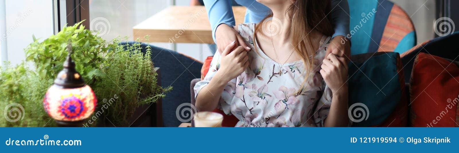 Möte av två flickvänner i ett kafé en kom upp bakom och kramat för att hälsa en annan flicka rymma för händer