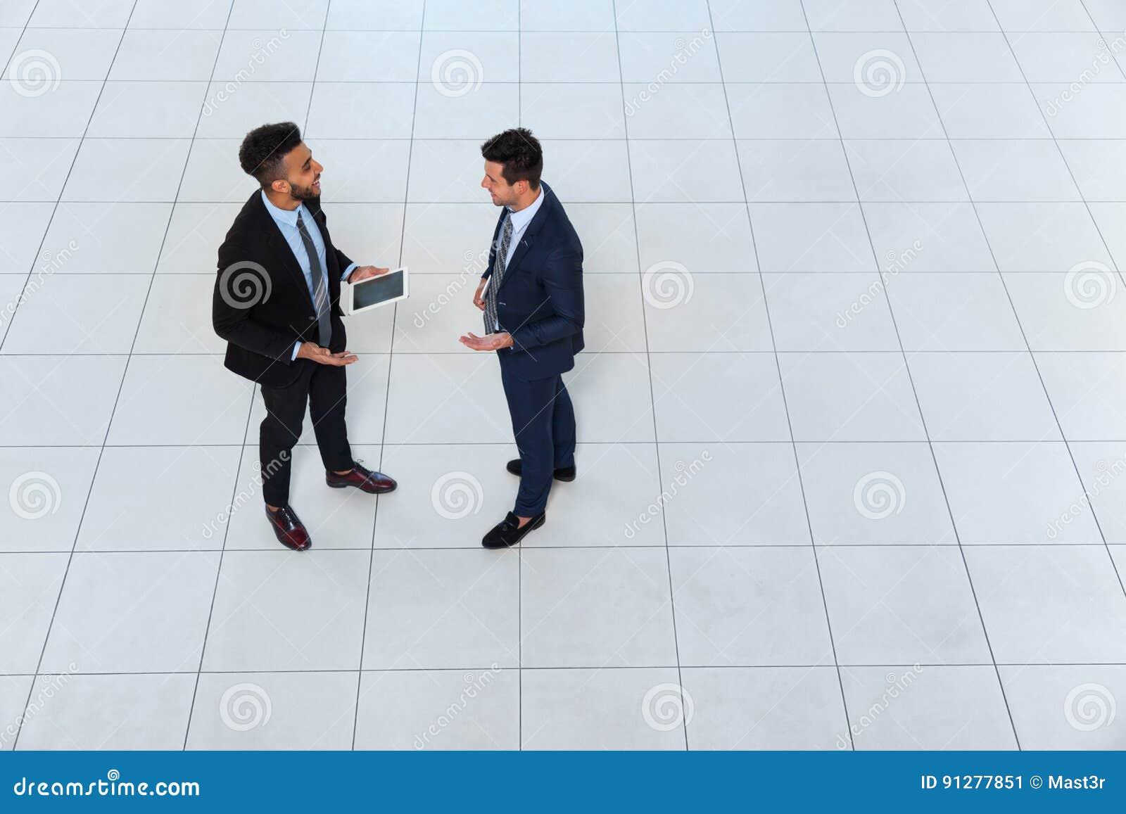 Möte för man för affär som två diskuterar projektplanet som meddelar, affärsmanTalking Top Angle sikt