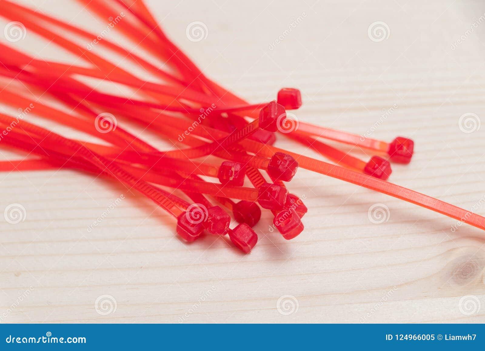 Múltiplo laço vermelho de muitos laços do fecho de correr isolado na madeira