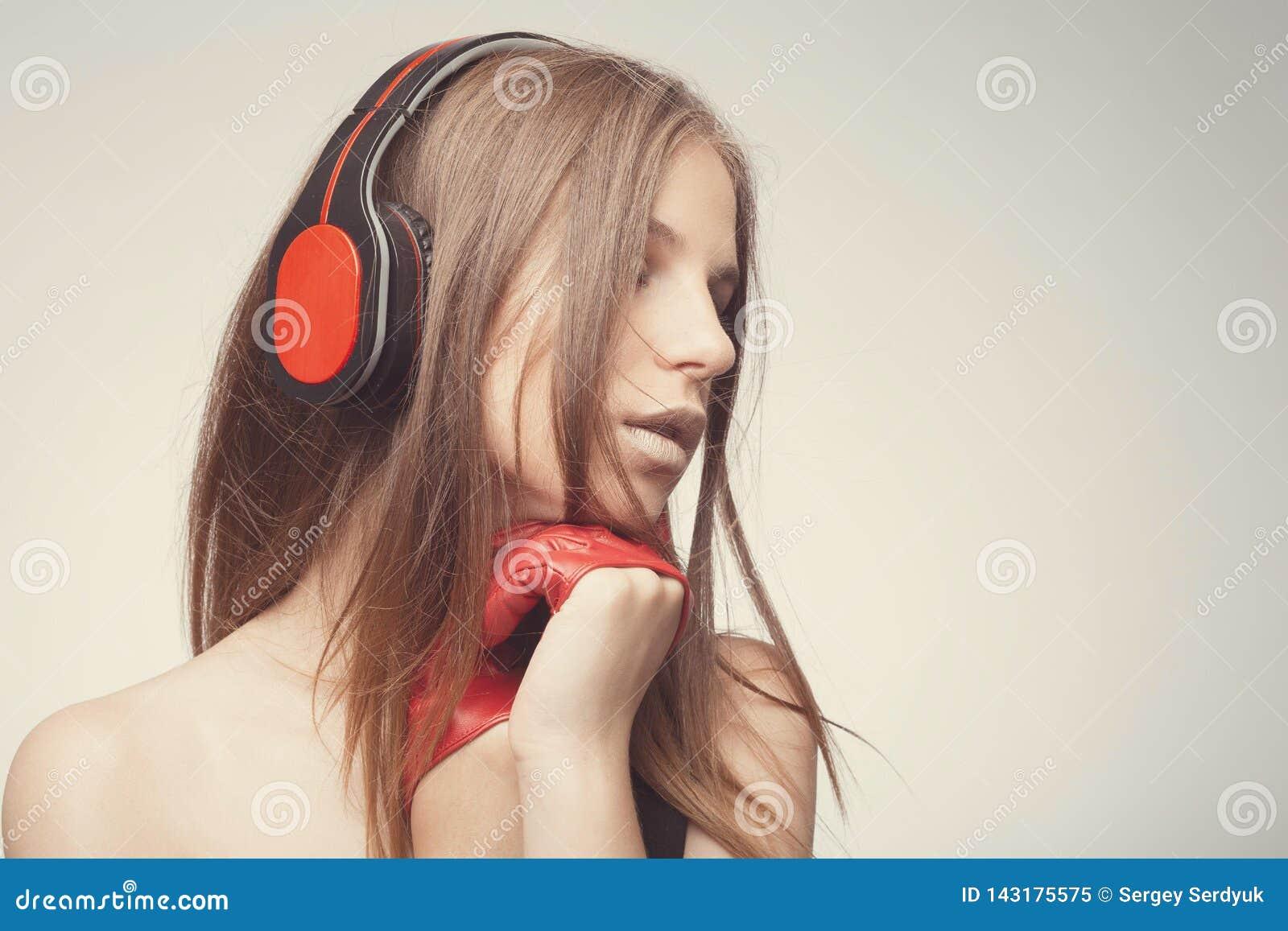 A música de escuta da menina bonita da forma com fones de ouvido, luvas vermelhas vestindo, toma o prazer com música Conceito da