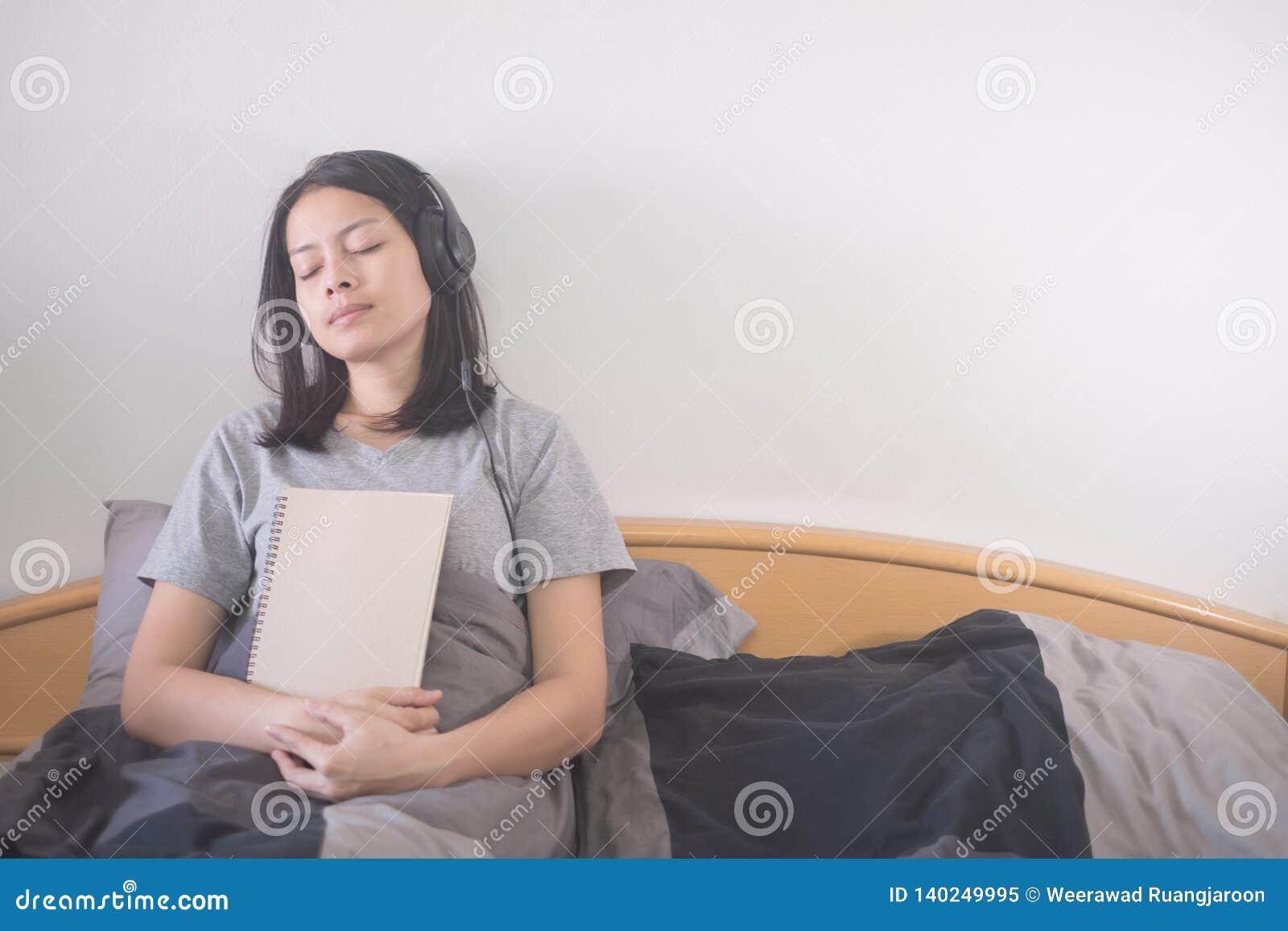 Música de escuta da mulher asiática bonita com o fones de ouvido e o livro de leitura que relaxam na cama