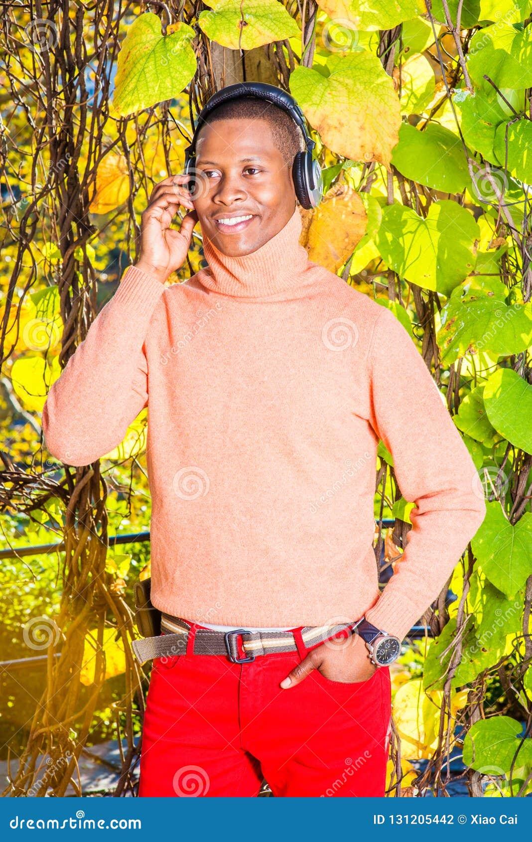 Música de escuta do homem afro-americano novo no Central Park, novo