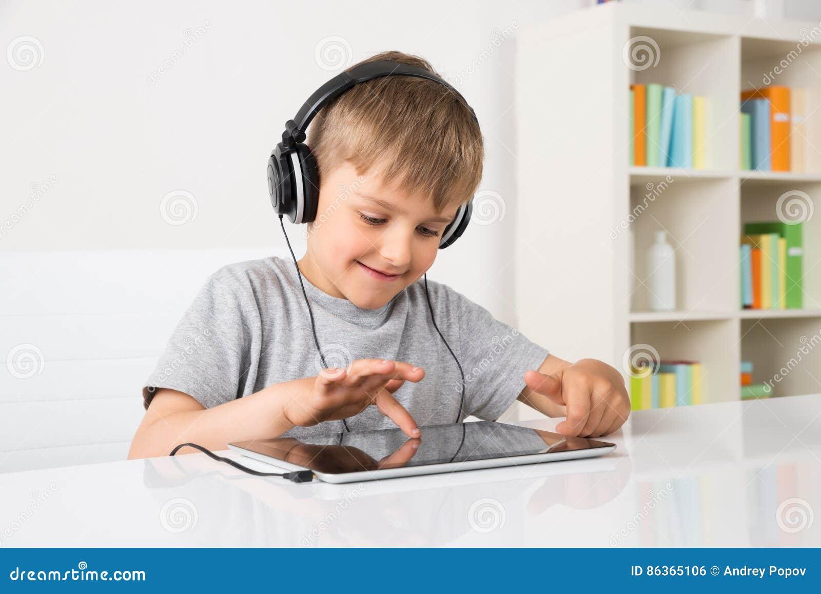 Música de escuta do menino na tabuleta de Digitas