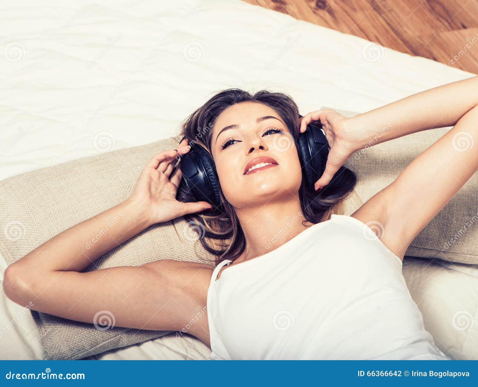 Música que escucha de los auriculares hermosos jovenes de la mujer en cama