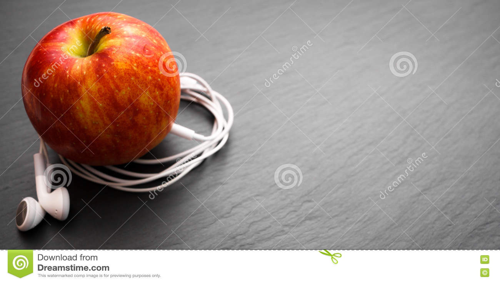 Música que juega la manzana en la cual los auriculares están conectados