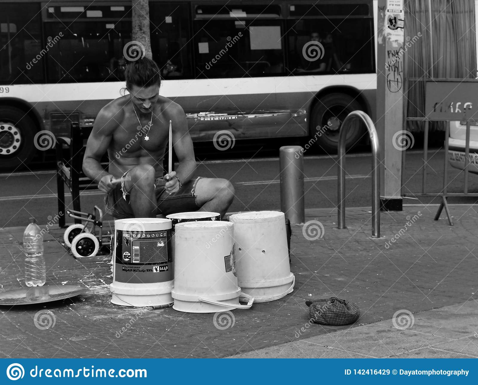 Músico considerável novo da rua, jogando cilindros em caixas do recipiente em um ajuste urbano na frente de um ônibus