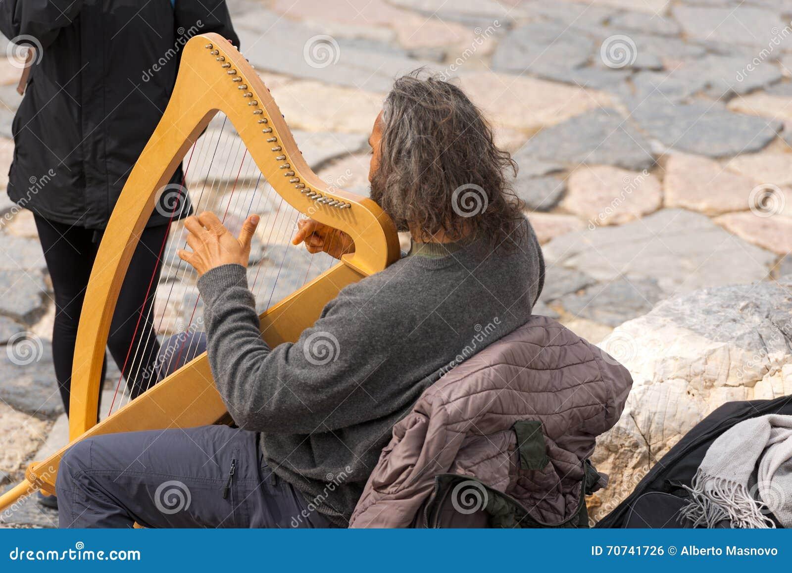 Músico Playing Classical Harp da rua