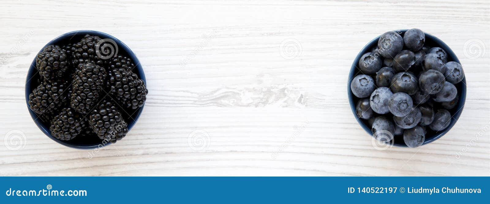 Mûres et myrtilles mûres dans des cuvettes bleues sur le fond en bois blanc, vue aérienne Baie d été De ci-dessus, plat, supérieu