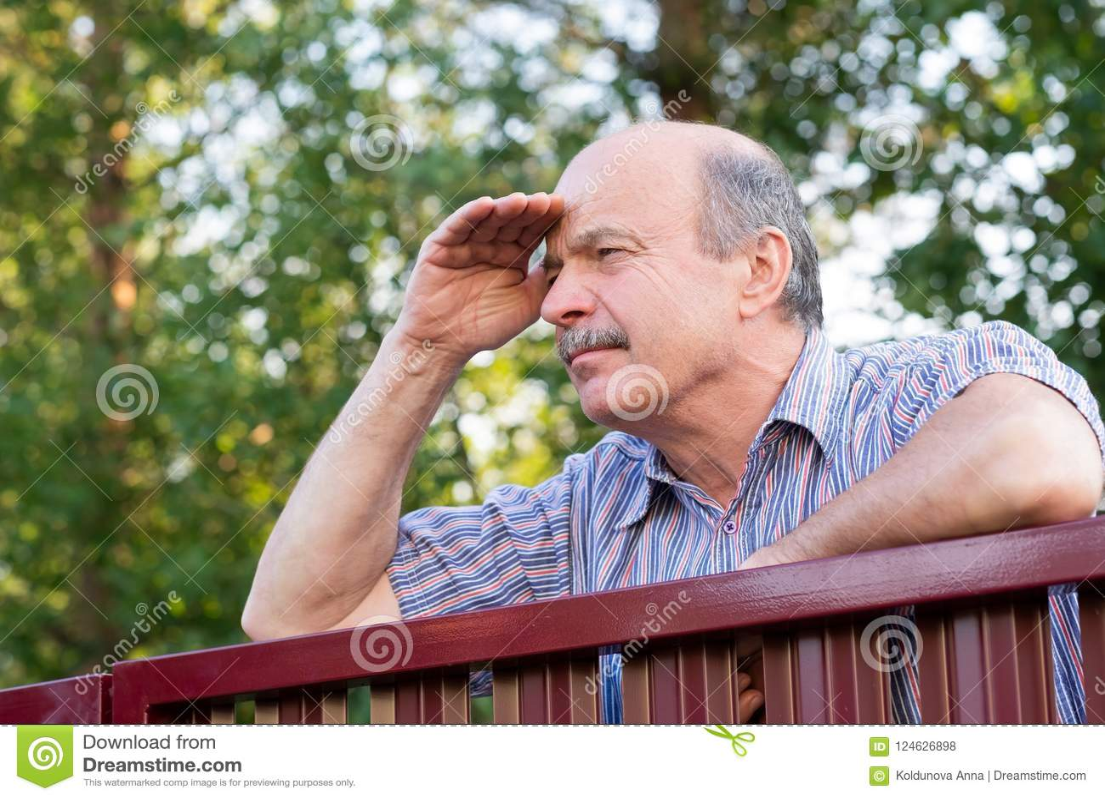 Mûrissez l homme caucasien observant soigneusement au-dessus de la barrière