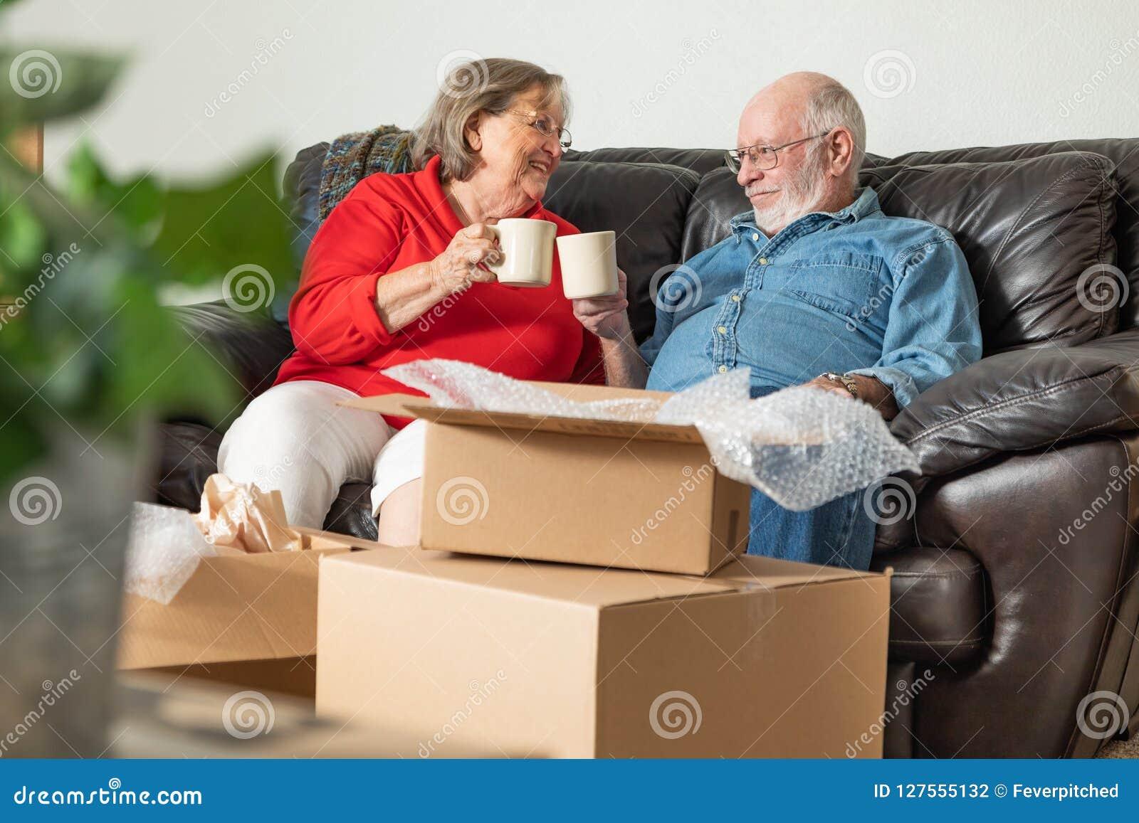 Müde ältere erwachsene Paare, die auf der Couch genießt Kaffee sich entspannen