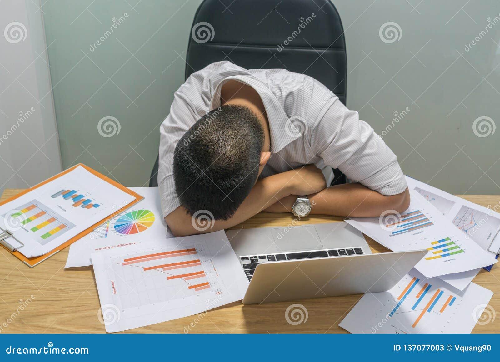 Müder Büromann, der kurzes am Arbeitsplatz ein Schläfchen hält