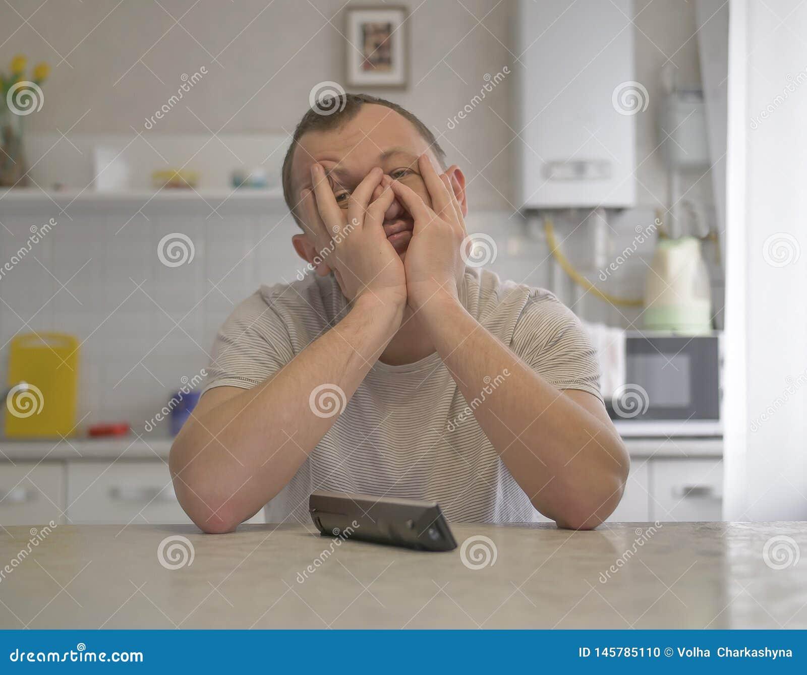 Müder junger Kerl, der auf dem Hintergrund der Küche sitzt