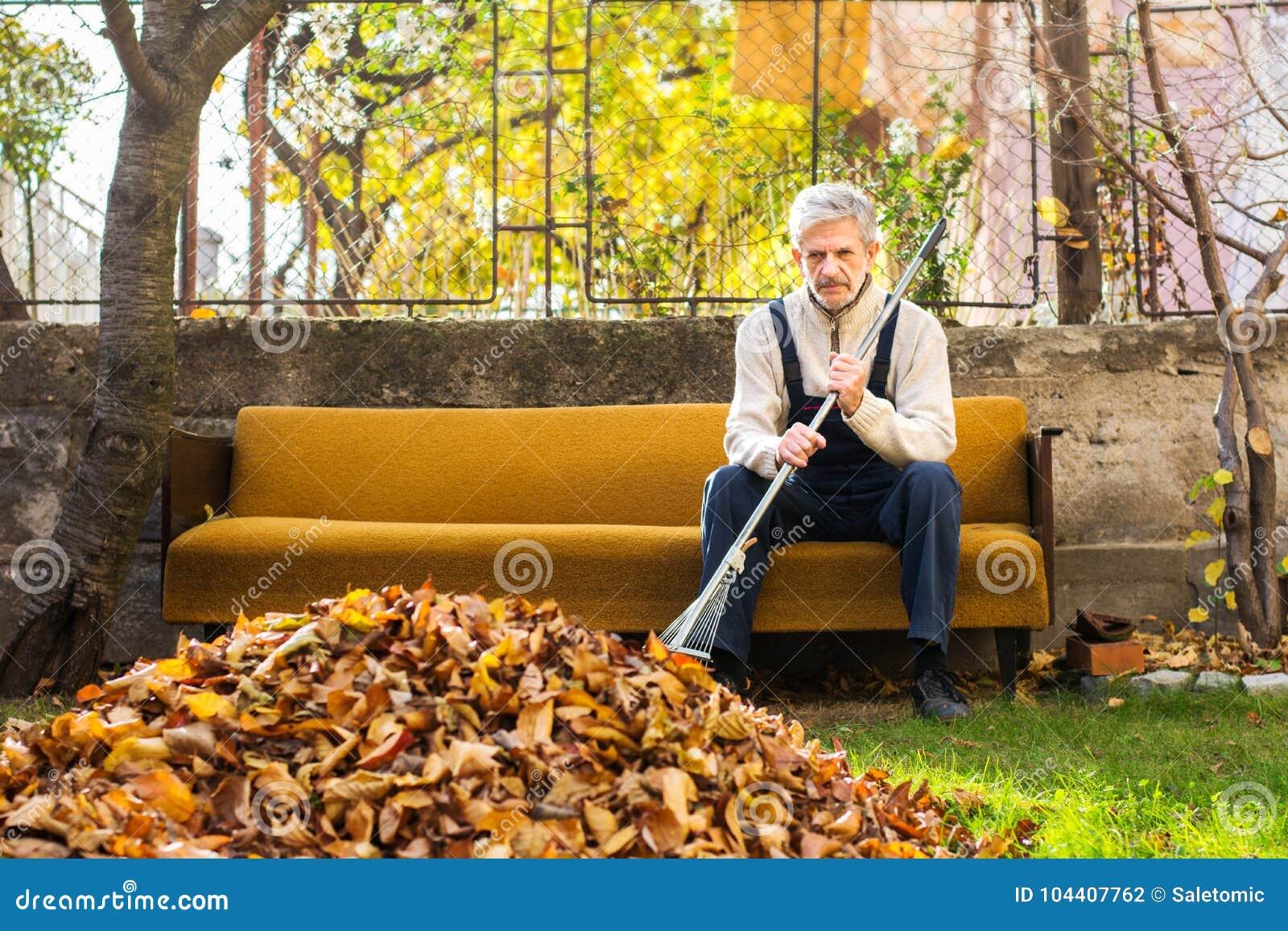 Müder Mann, der Pause von Reinigung gefallenem Herbstlaub in macht