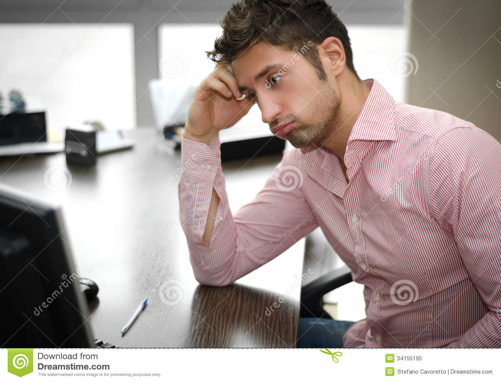 Müder oder frustrierter Büroangestellter, der Bildschirm betrachtet