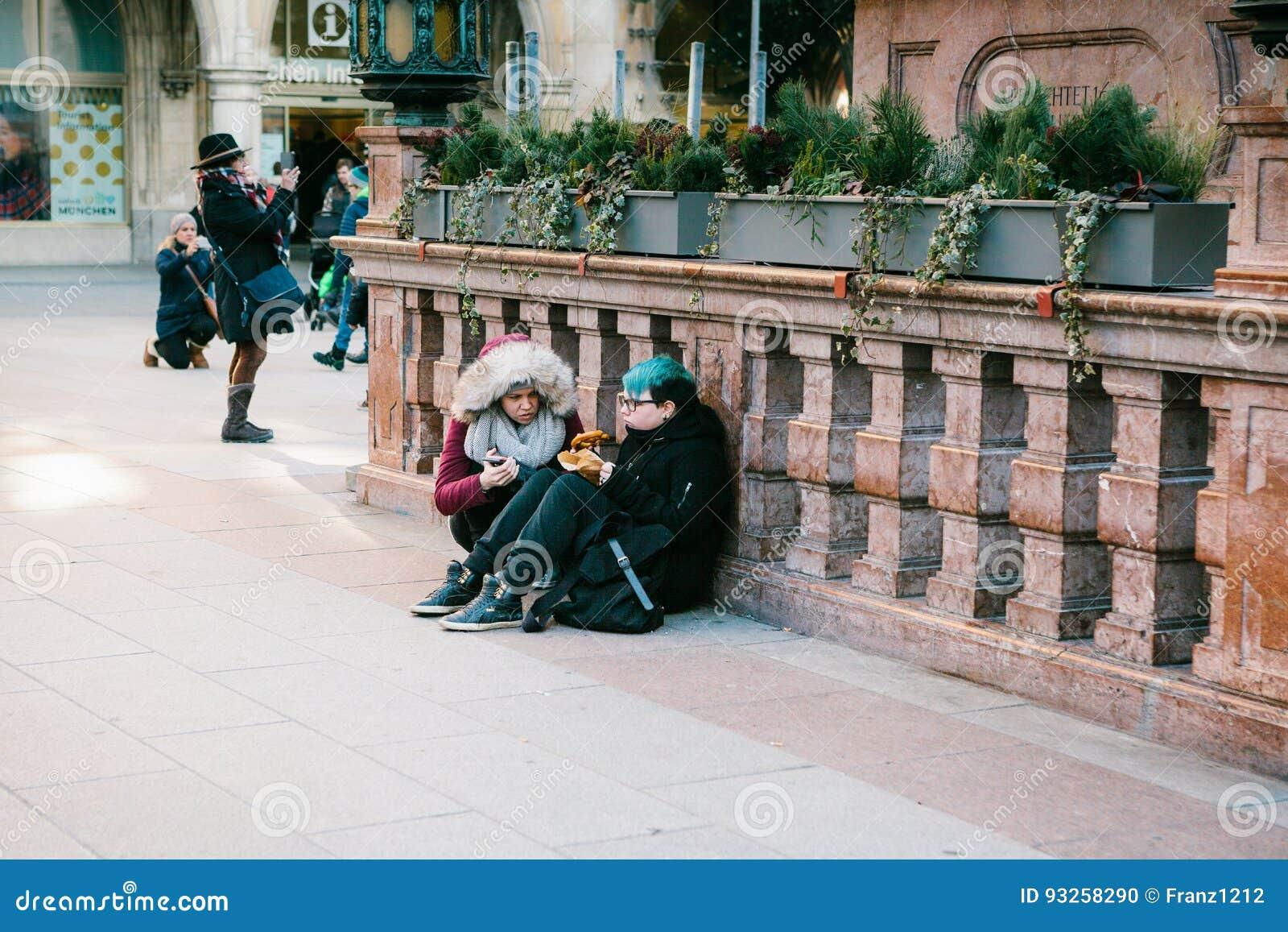 München, Duitsland, 29 December, 2016: Twee punkmeisjes zitten en eten in het centrale vierkant in München subcultuur everyday