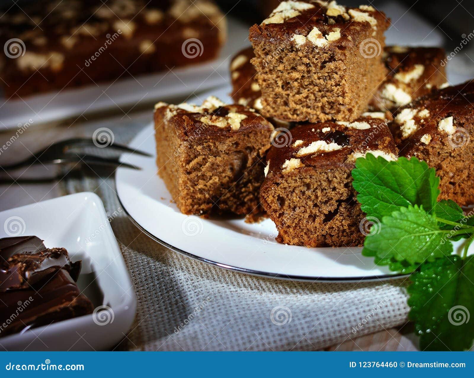 München-Torte, frische tadellose Blätter, Stücke Schokolade, Leinenserviette, Holztisch