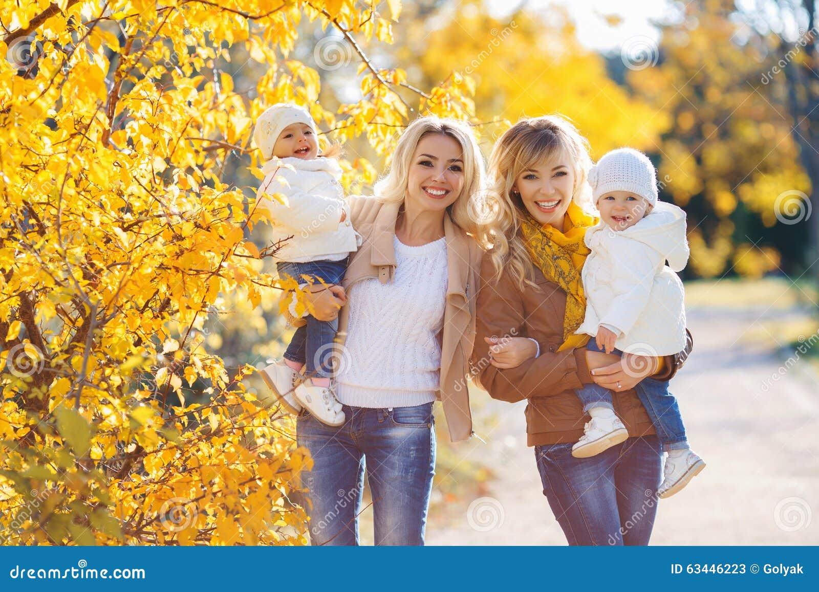 Mütter und Kinder für einen Weg im Park im Herbst