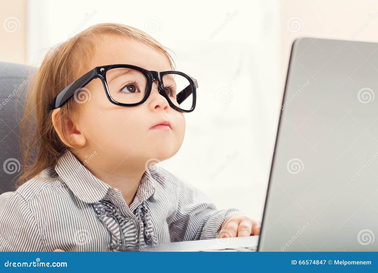Mądrze berbeć dziewczyna jest ubranym dużych szkła podczas gdy używać jej laptop