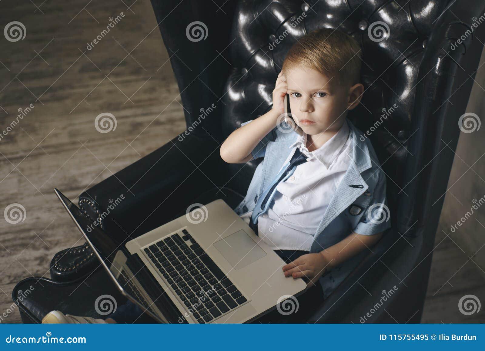 Mądrze mała berbeć chłopiec pije kawę z dużymi szkłami podczas gdy używać jej laptop