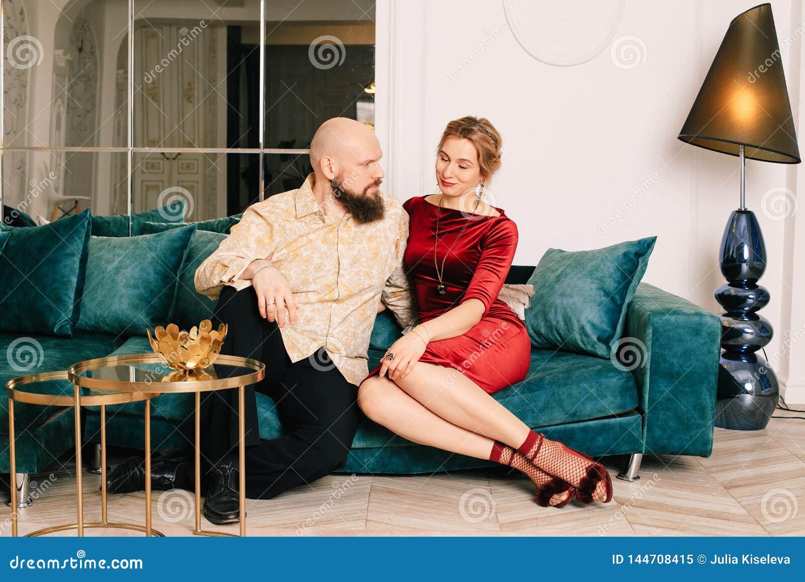 Męża i żony obsiadanie na leżance w przestronnym jaskrawym pokoju Cieszy się każda minuta wpólnie
