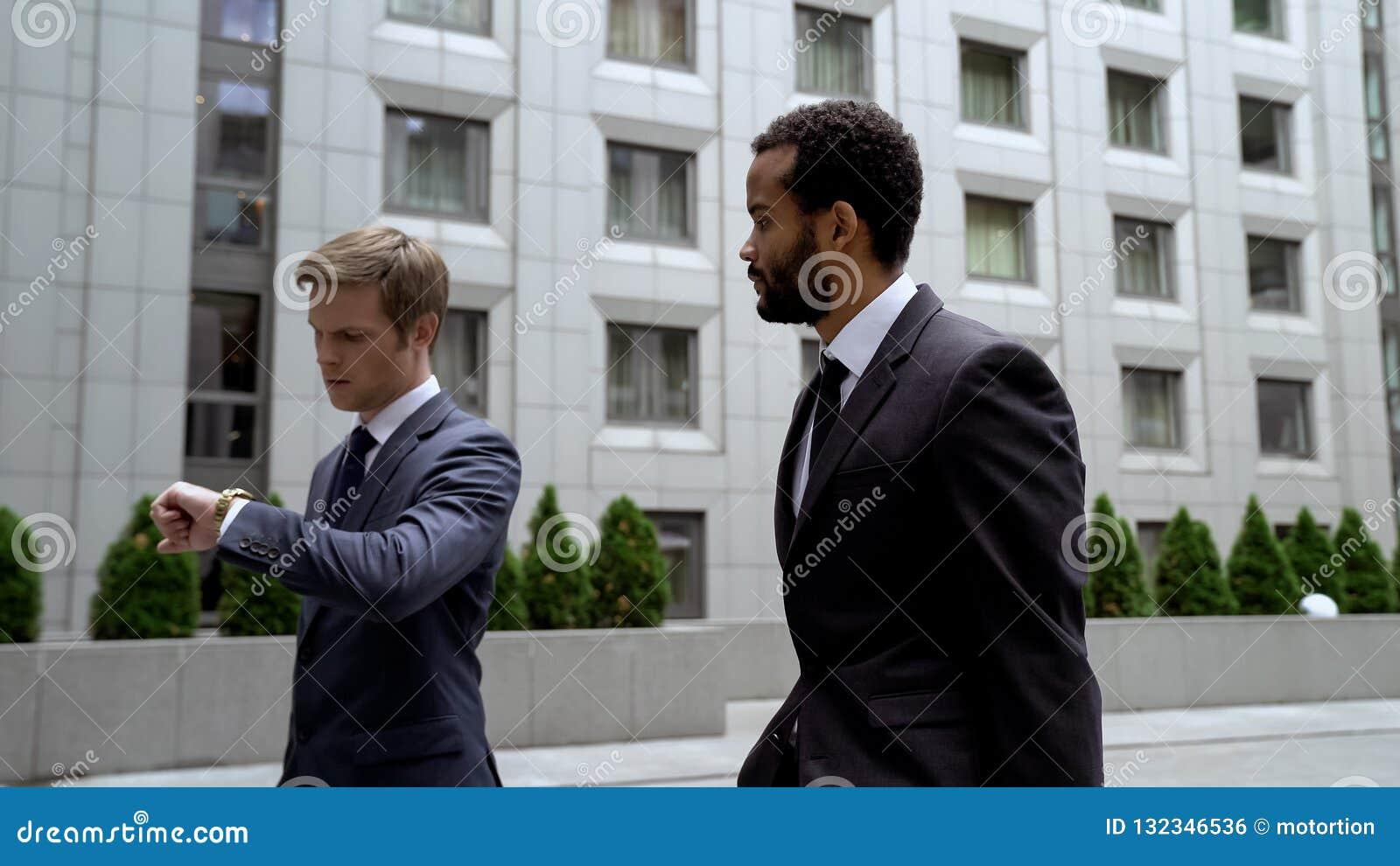 Mężczyźni iść znacząco biznesowy spotkanie, patrzeje zegarek, czasu zarządzanie