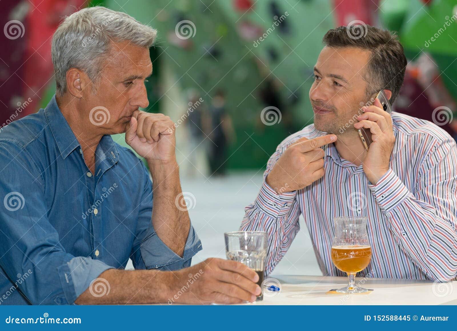 Mężczyźni opowiada na telefonie siedzieli mieć napój jeden