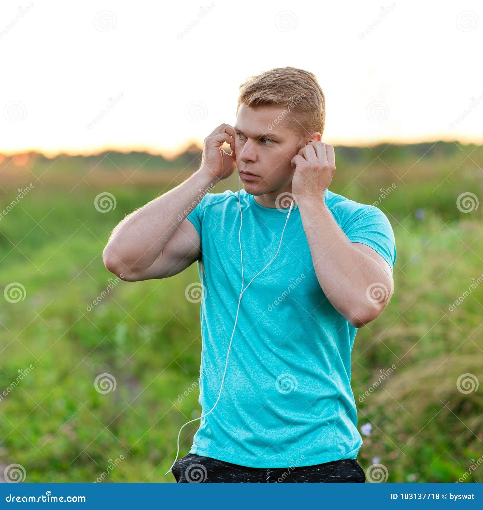 Mężczyzna atlen stojaki w park sukniach hełmofony, ufny spojrzenie Lato styl życia, motywacja jest silny kardigan