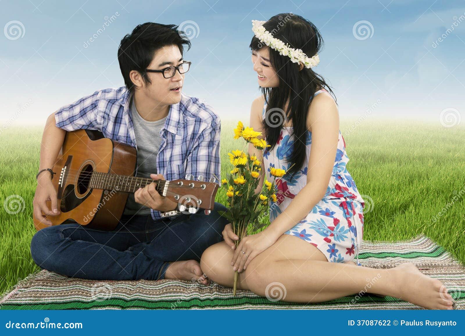 Download Mężczyzna Bawić Się Gitarę Dla Jego Dziewczyny Zdjęcie Stock - Obraz złożonej z świętowanie, trawy: 37087622