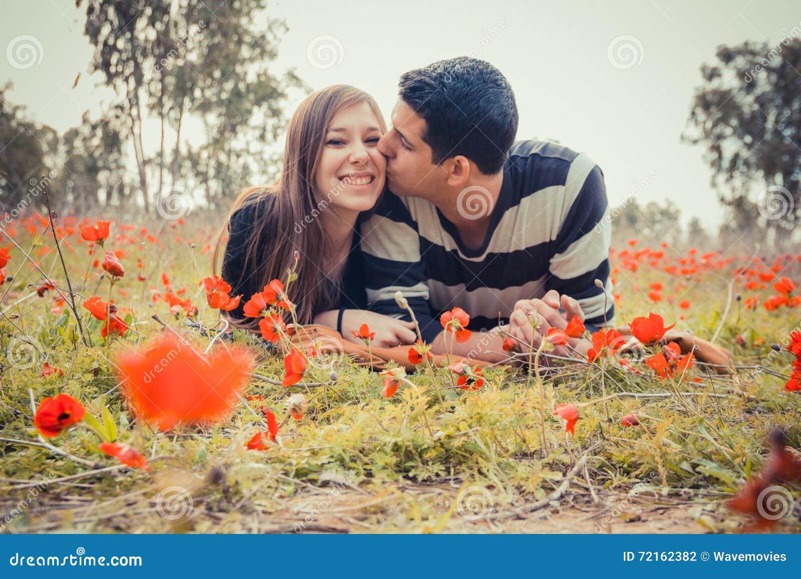 Mężczyzna całowania ona i kobieta toothy uśmiech podczas gdy one kłaść o