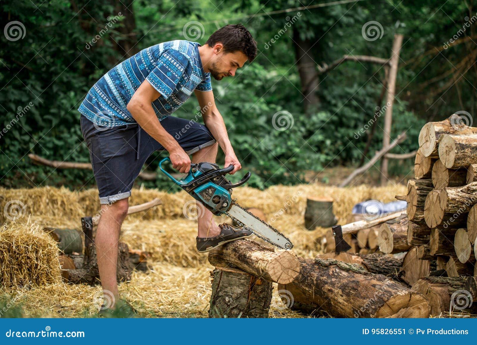 Mężczyzna ciapania drewno z piłą łańcuchową