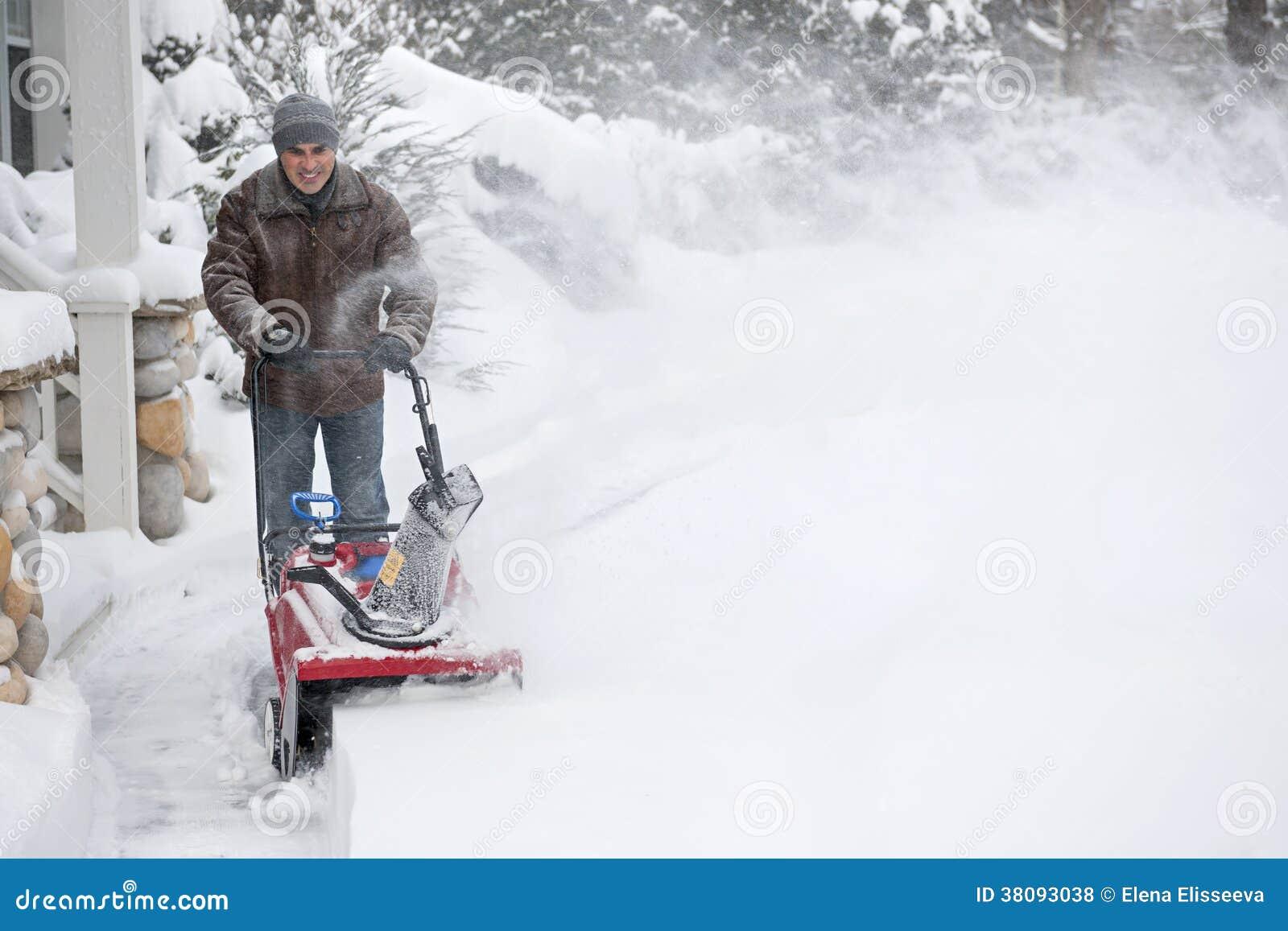 Mężczyzna clearingowy podjazd z snowblower