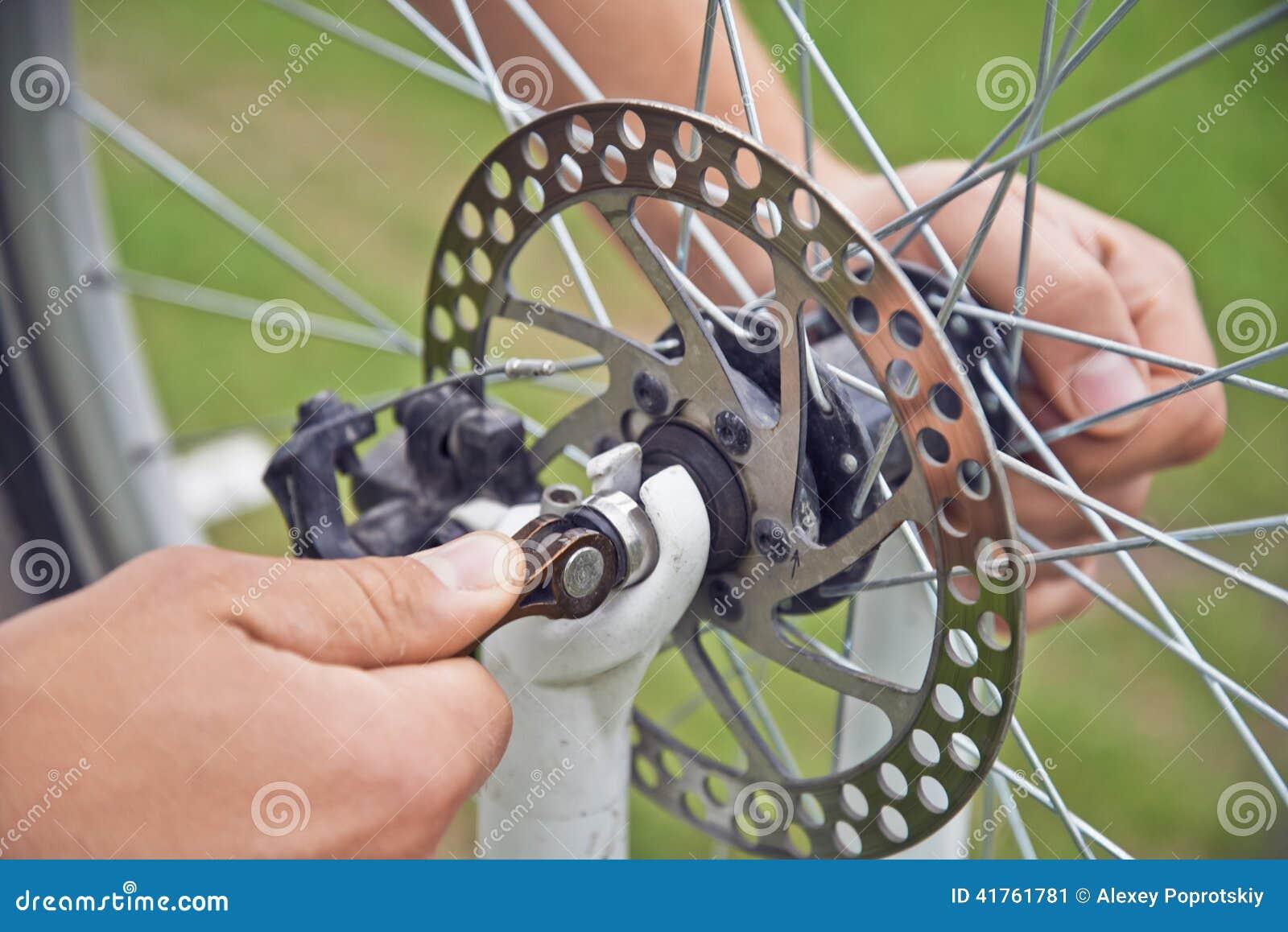 Mężczyzna cyklista sprawdza hamulcowego koło bicykl