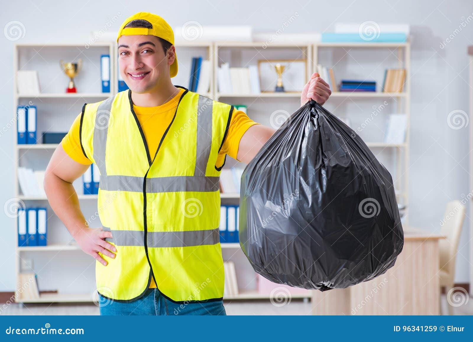 Mężczyzna czyści biuro i trzyma torba na śmiecie