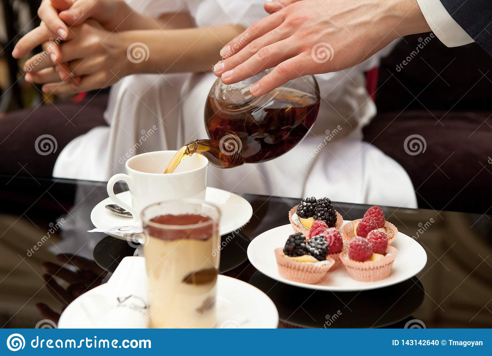 Mężczyzna dba dla kobiety: nalewa ona zielonej herbaty Na stole są desery: tiramisu i ciasta z świeżymi jagodami Bez twarzy