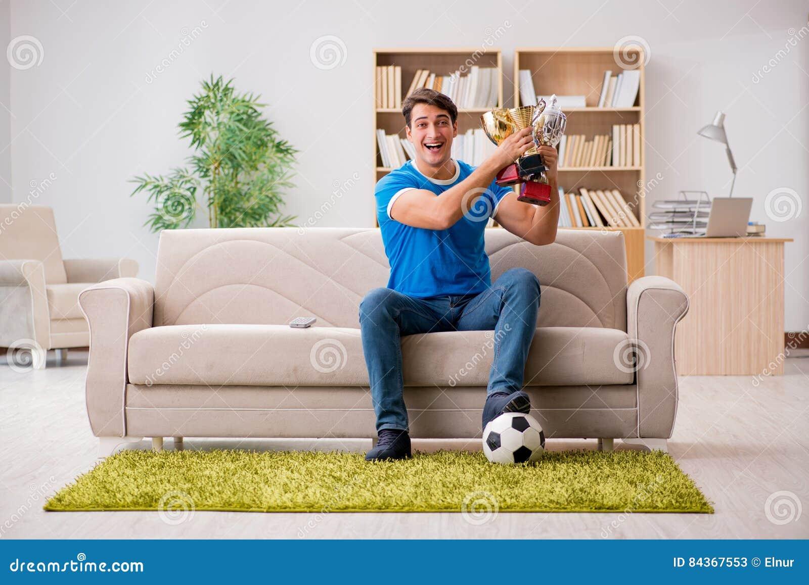 Mężczyzna dopatrywania futbol w domu