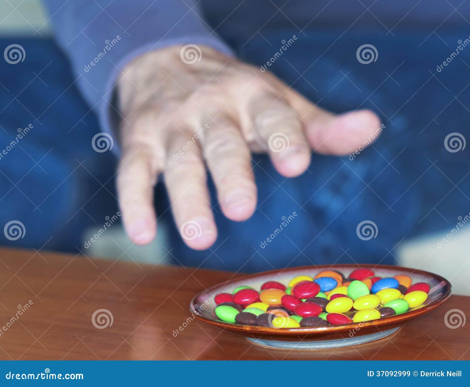 Download Mężczyzna Dosięga Dla Barwionych Cukierków W Naczyniu Obraz Stock - Obraz złożonej z kurenda, okrąg: 37092999